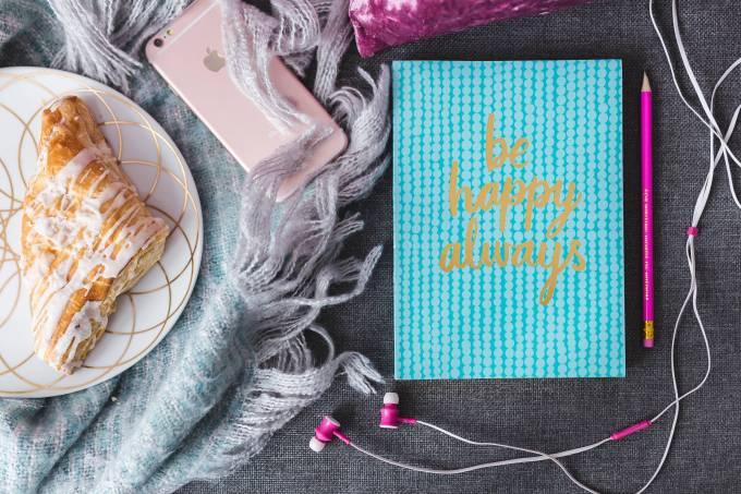 kaboompics_Blue notebook with a pink iPhone, headphones and a sweet bun